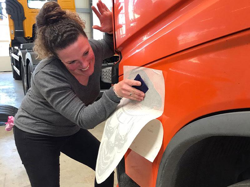 Unsere Mitarbeiterin während sie die LKW-Beschriftung auf die Fahrerseite klebt.