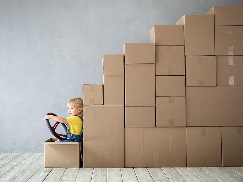 Kind mit Lenkrad sintz in Kartonstapel, die aussehen wie ein LKW